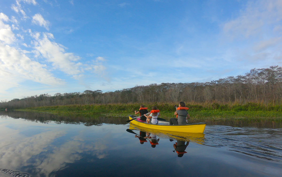 Three people in yellow canoe at the shore line near  Blue Spring State Park, Florida