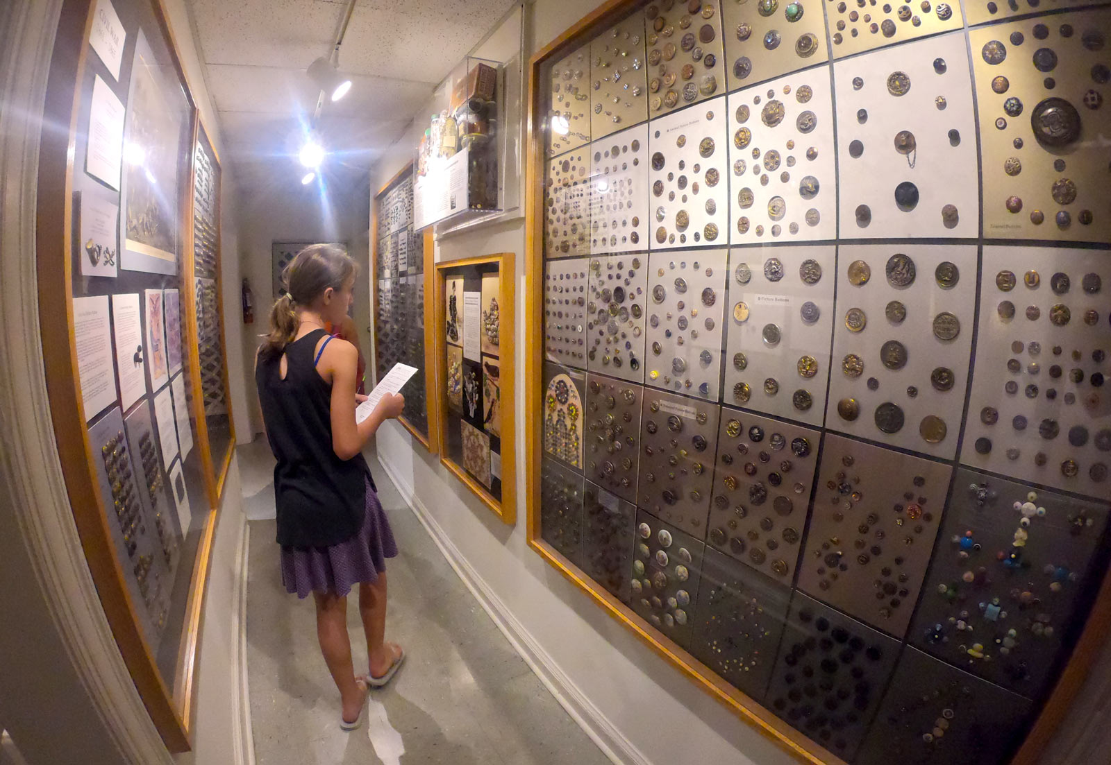 Young girl looking at button collections on walls of Lightner Museum in Saint Augustine, Florida