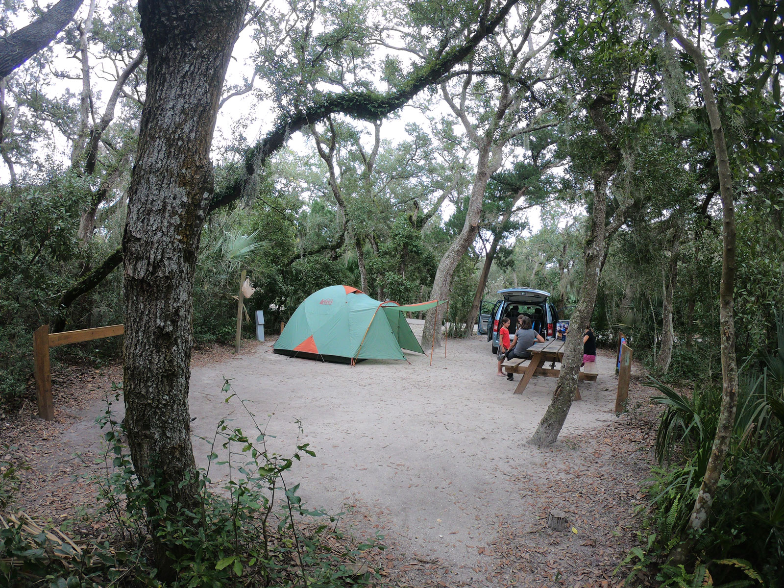 Anastasia State Park campsite with picnic table, green tent, van, and campers