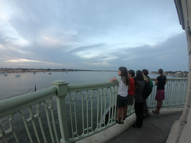 Five people leaning on railing watching the boats in the Matanzas River near St. Augustine, Florida