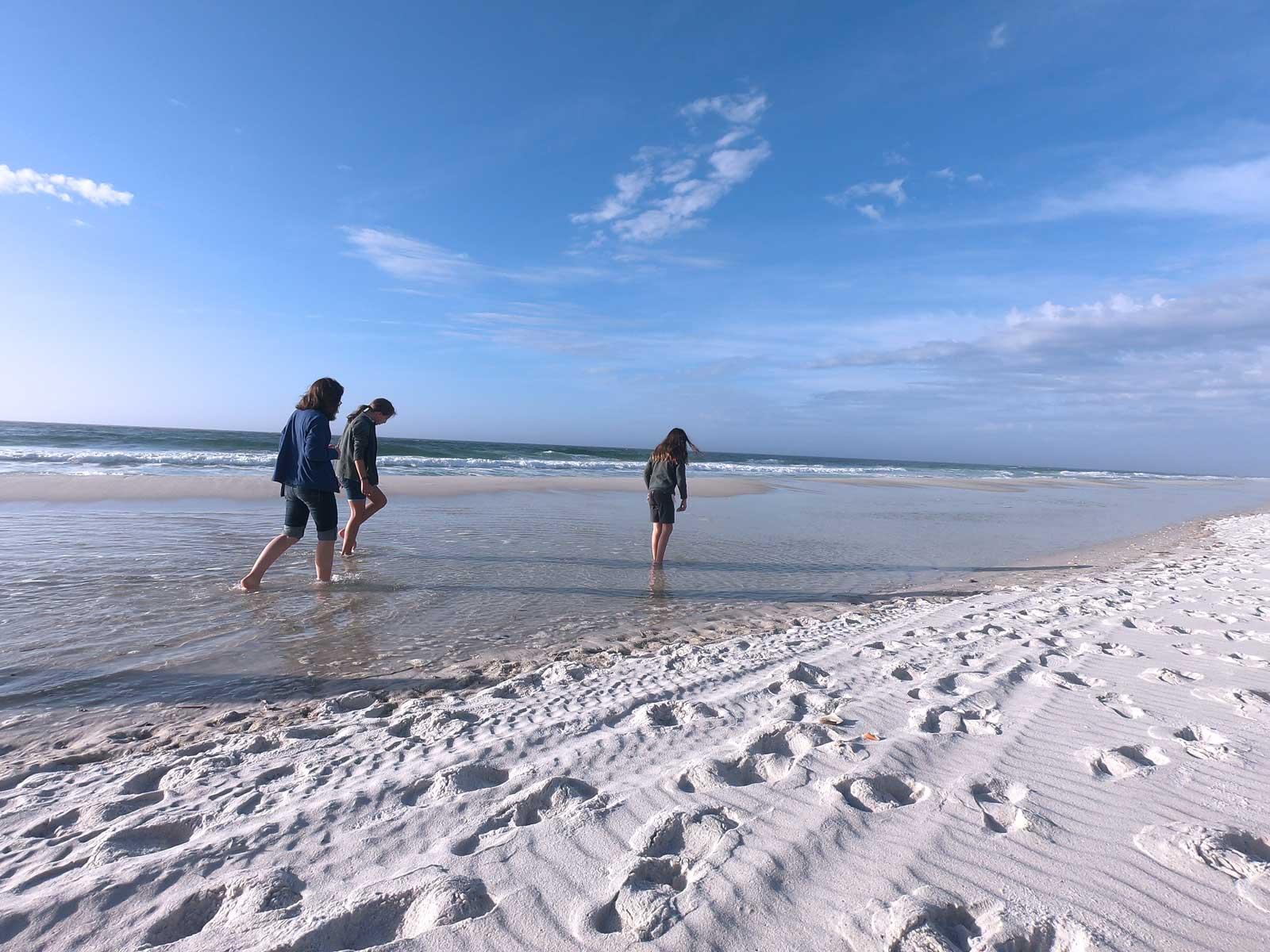 Three girls wading in ocean on Pensacola Beach, Florida