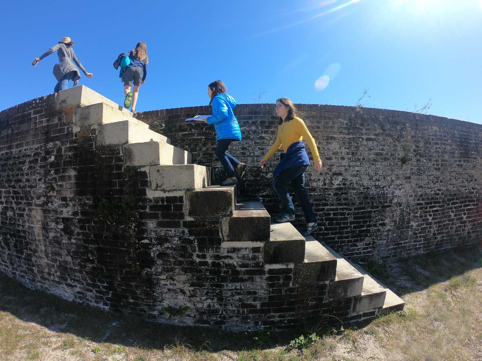 Four girls climbing stairs at Fort Pickens, Pensacola Beach, Florida