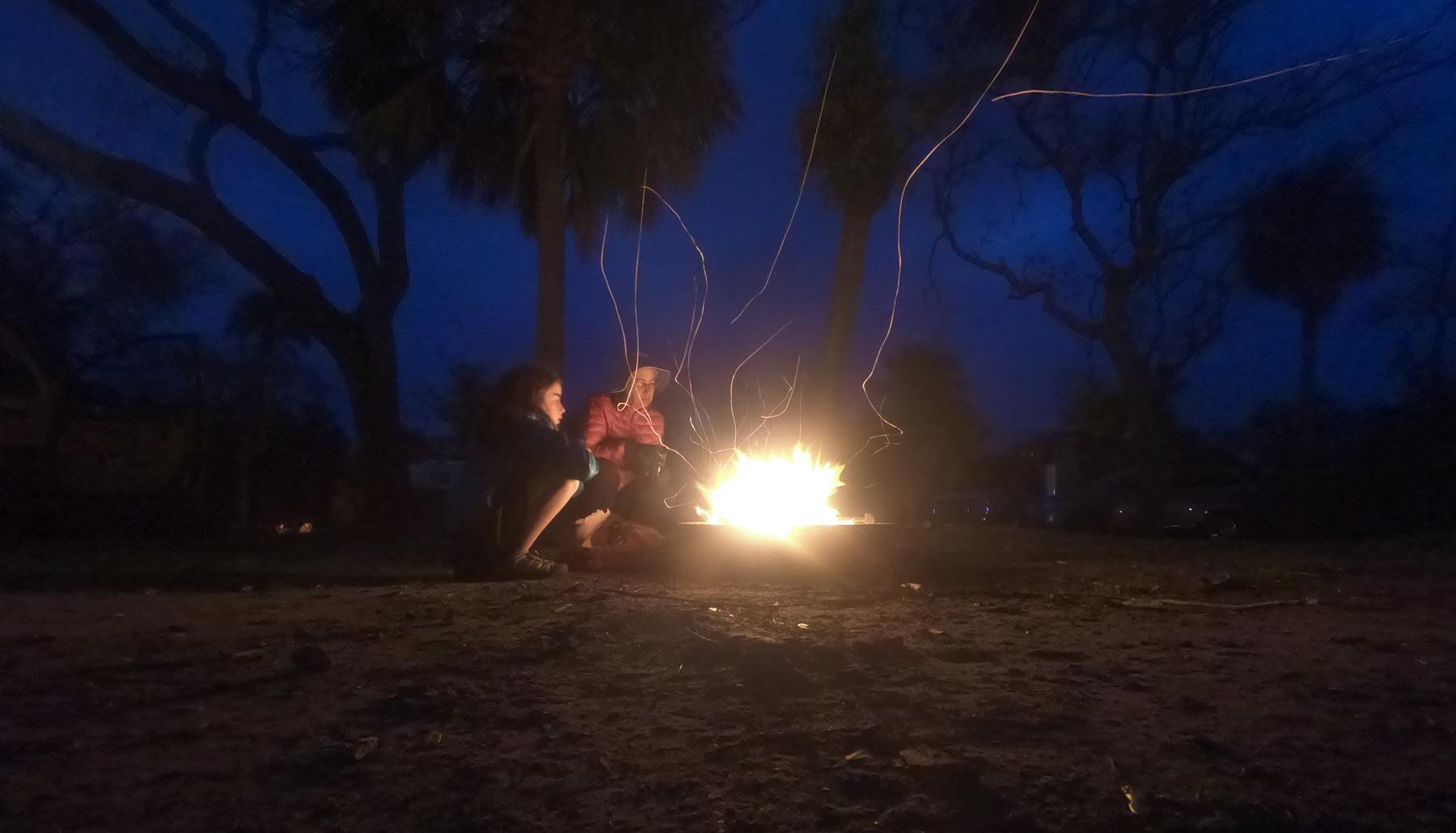 Family gathered around glowing campfire at night at Hunting Island State Park, South Carolina