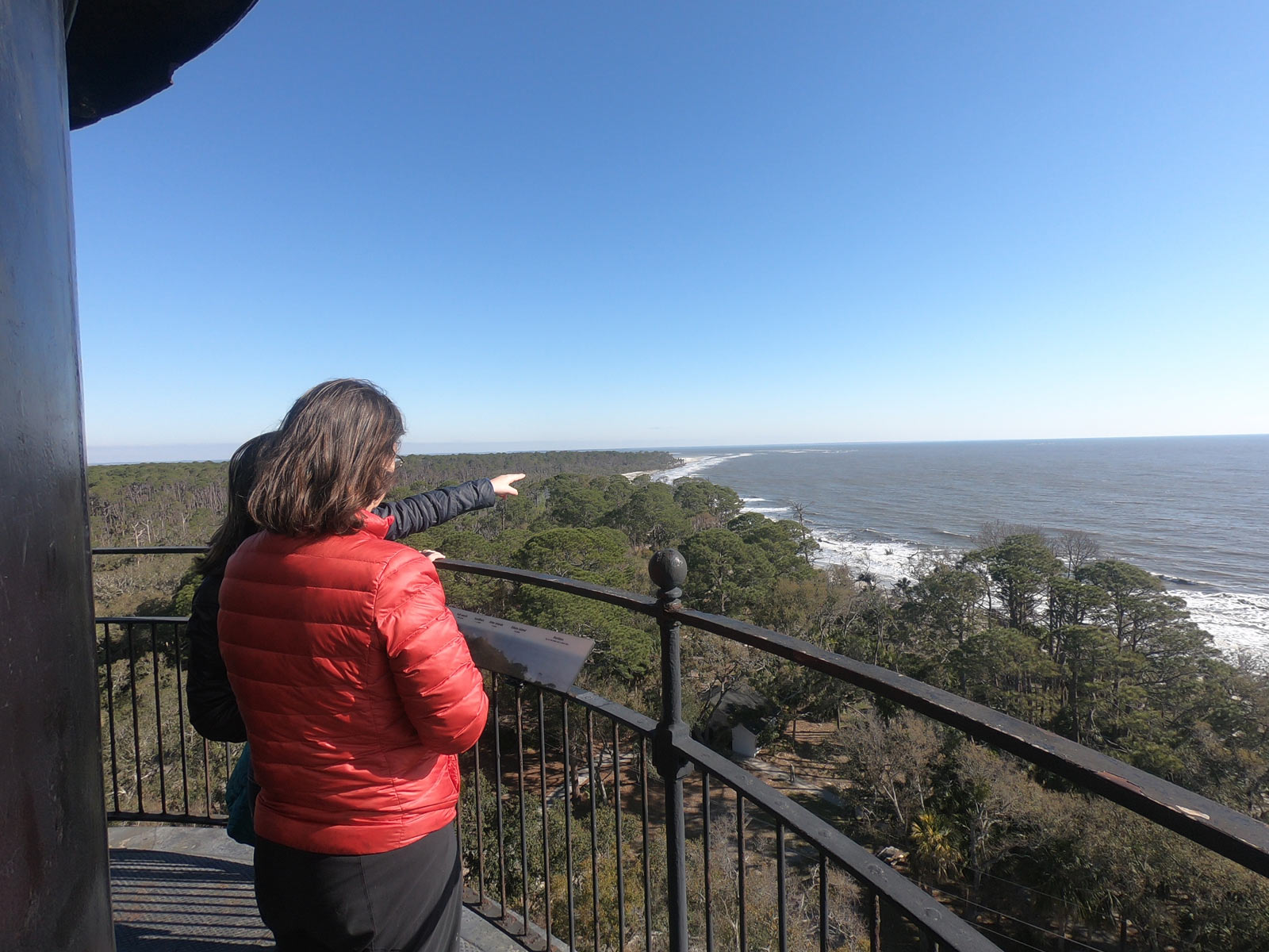 Two people looking out from top of lighthouse at the Atlantic Ocean in Hunting Island State Park, South Carolina