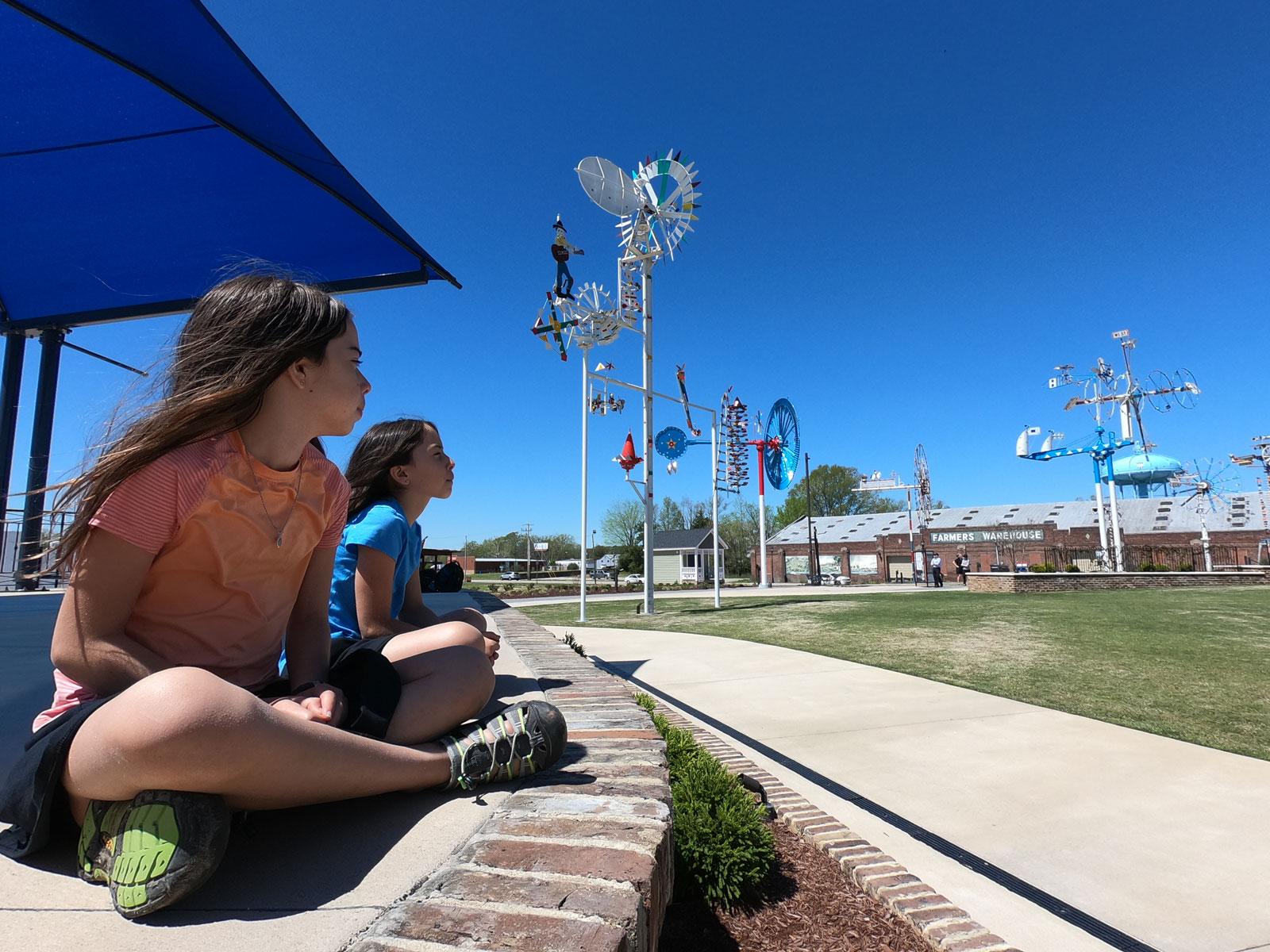 Two girls sitting in Vollis Simpson Whirligig Park, Wilson, North Carolina