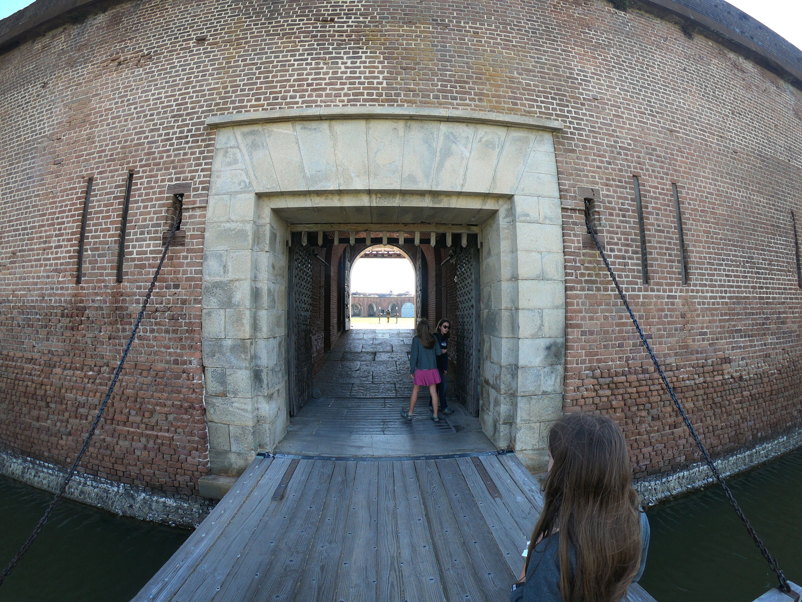 Three girls on drawbridge near moat gate at Fort Pulaski National Monument, Georgia