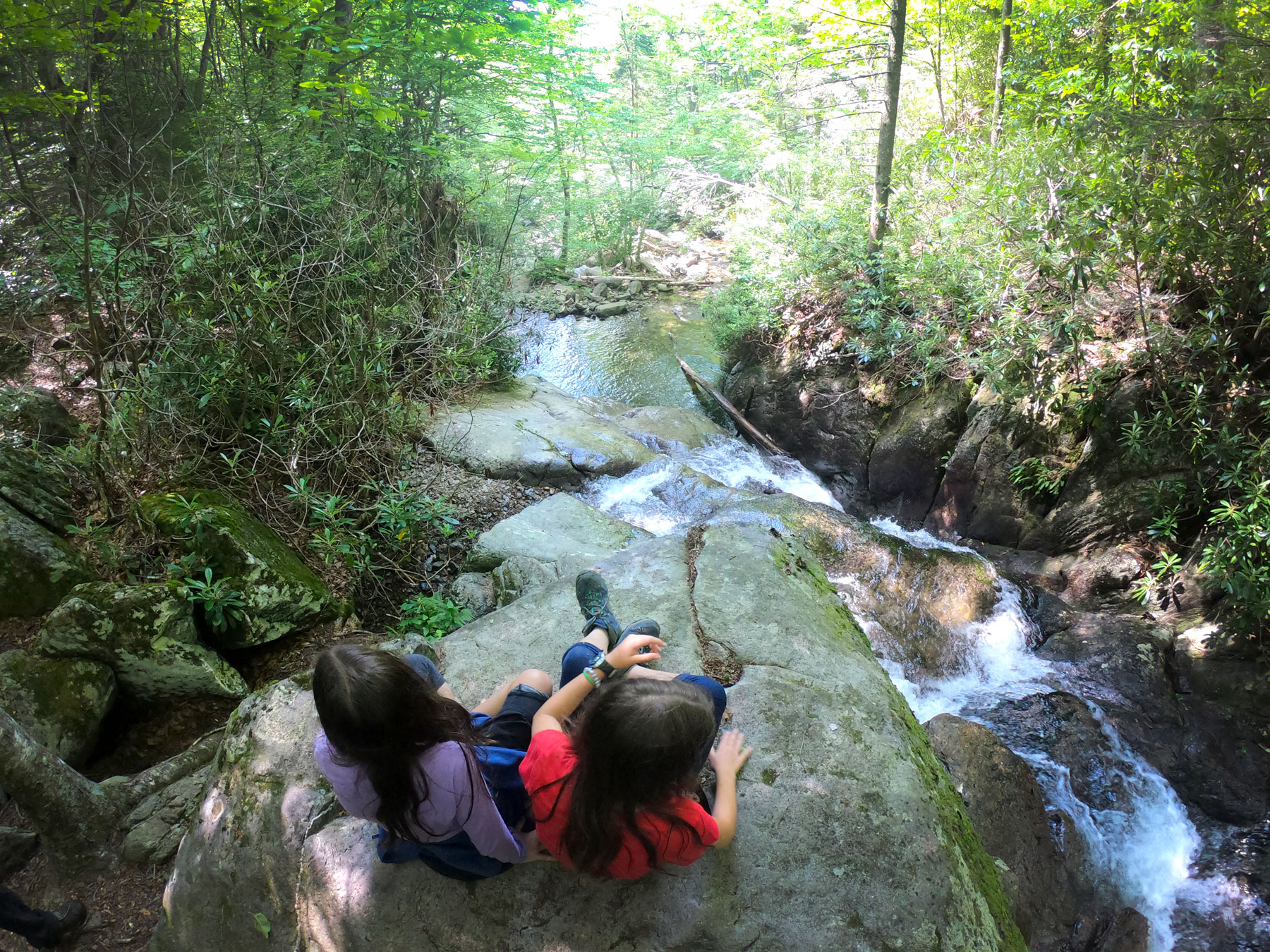 Two girls sitting on bouldering overlooking the Cabin Creek waterfall while camping at Grayson Highlands State Park, Virginia