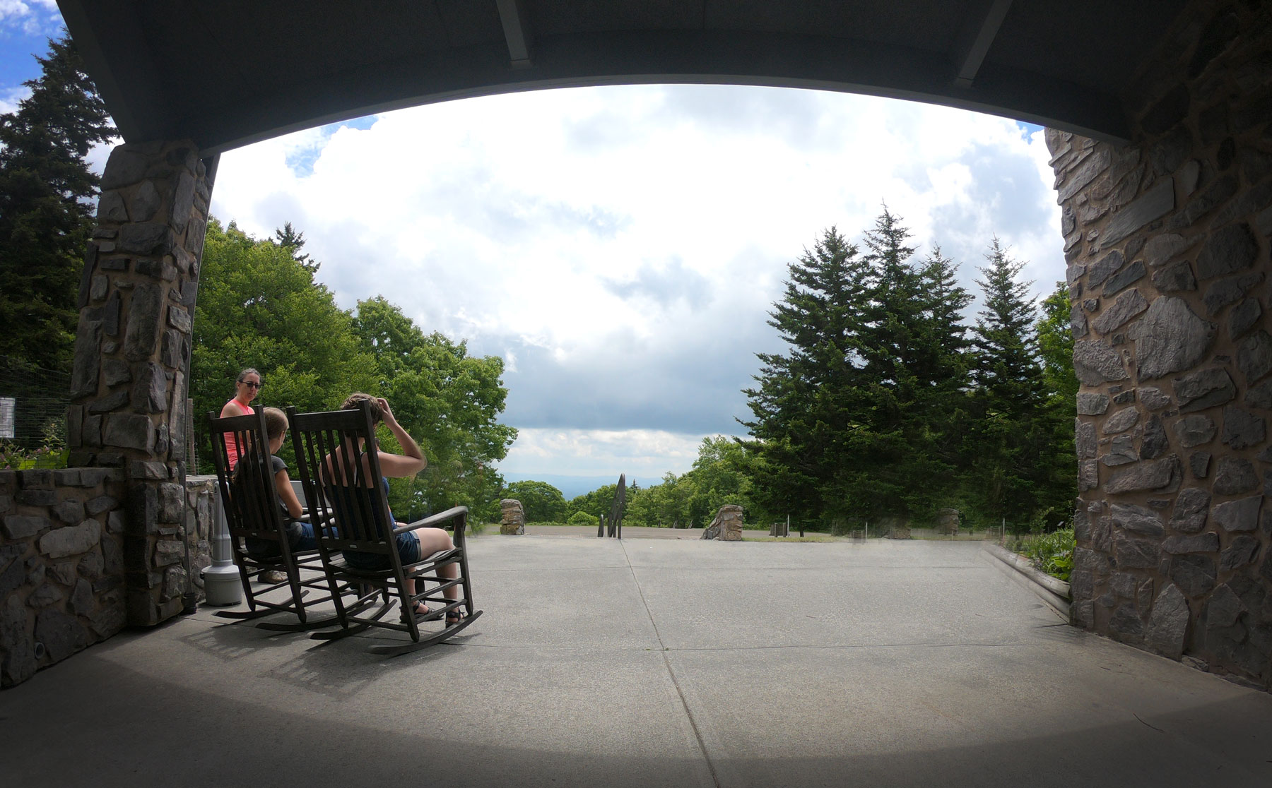 Family sitting in the rocking chairs under the shelter of the Grayson Highlands State Park, Virginia