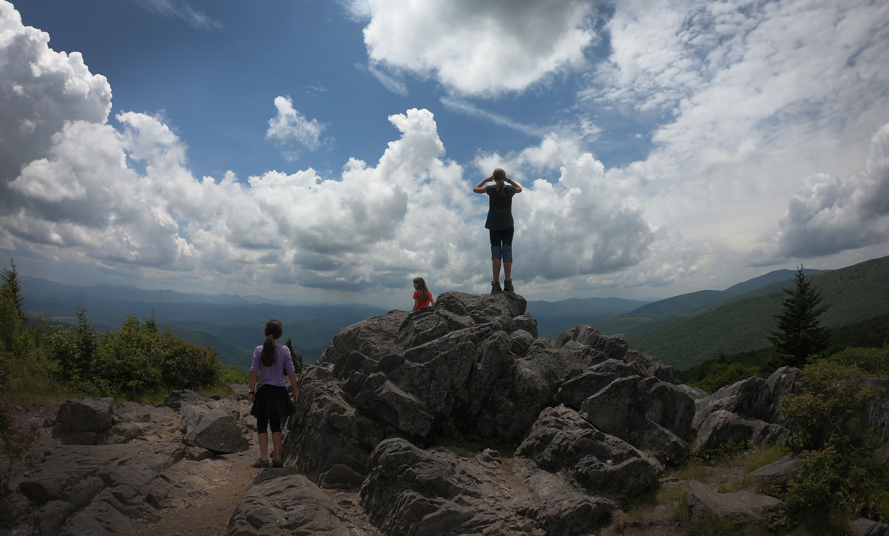 Three kids looking over summit boulders while camping in Grayson Highlands State Park, Virginia