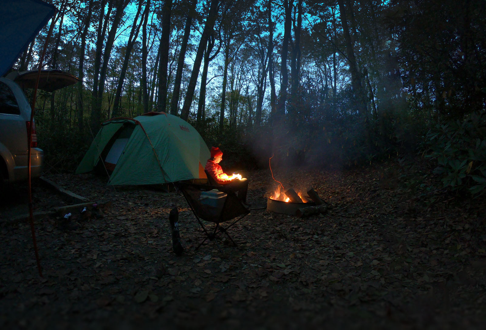 Woman sitting by the fire while camping in Julian Price Campground