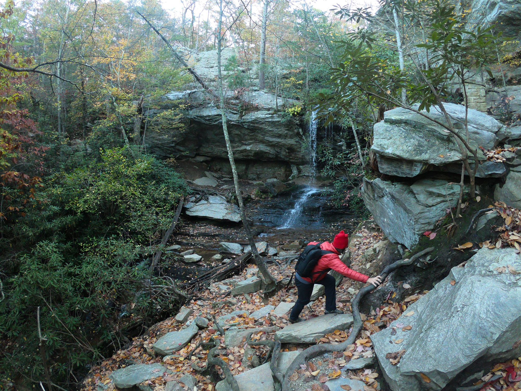 Woman in red hiking Window Falls and Hidden Falls while camping in Hanging Rock State Park, North Carolina