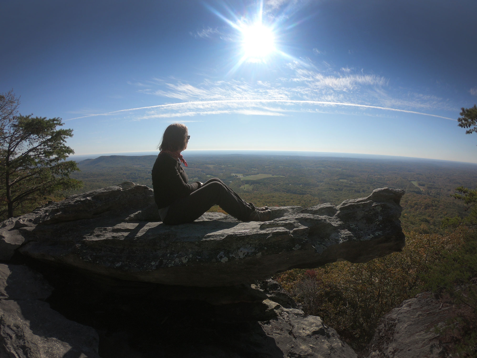 Woman on Wolf Rock outcropping while camping in Hanging Rock State Park, North Carolina