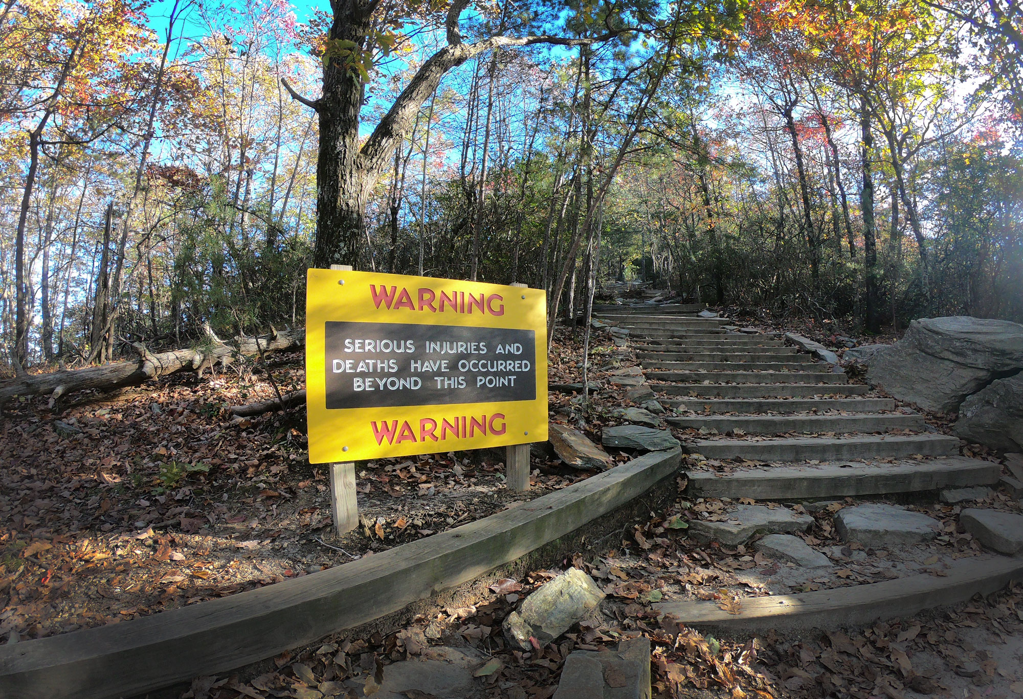 Yellow warning sign for serious injuries on Hanging Rock Trail while camping in Hanging Rock State Park, North Carolina