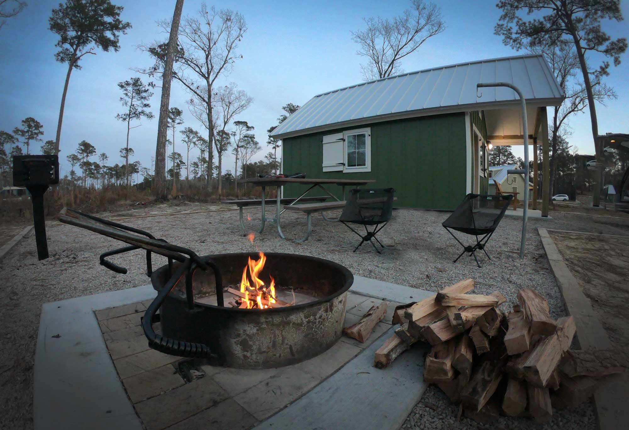 Evening at Goose Creek State Park camping cabin with fire pit, picnic table, lantern hook, and grill in North Carolina