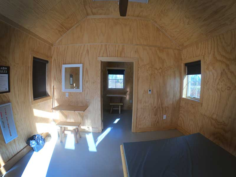 Interior view of queen bed, desk, mirror, and vaulted ceilings in the camping cabins at Goose Creek State Park, North Carolina