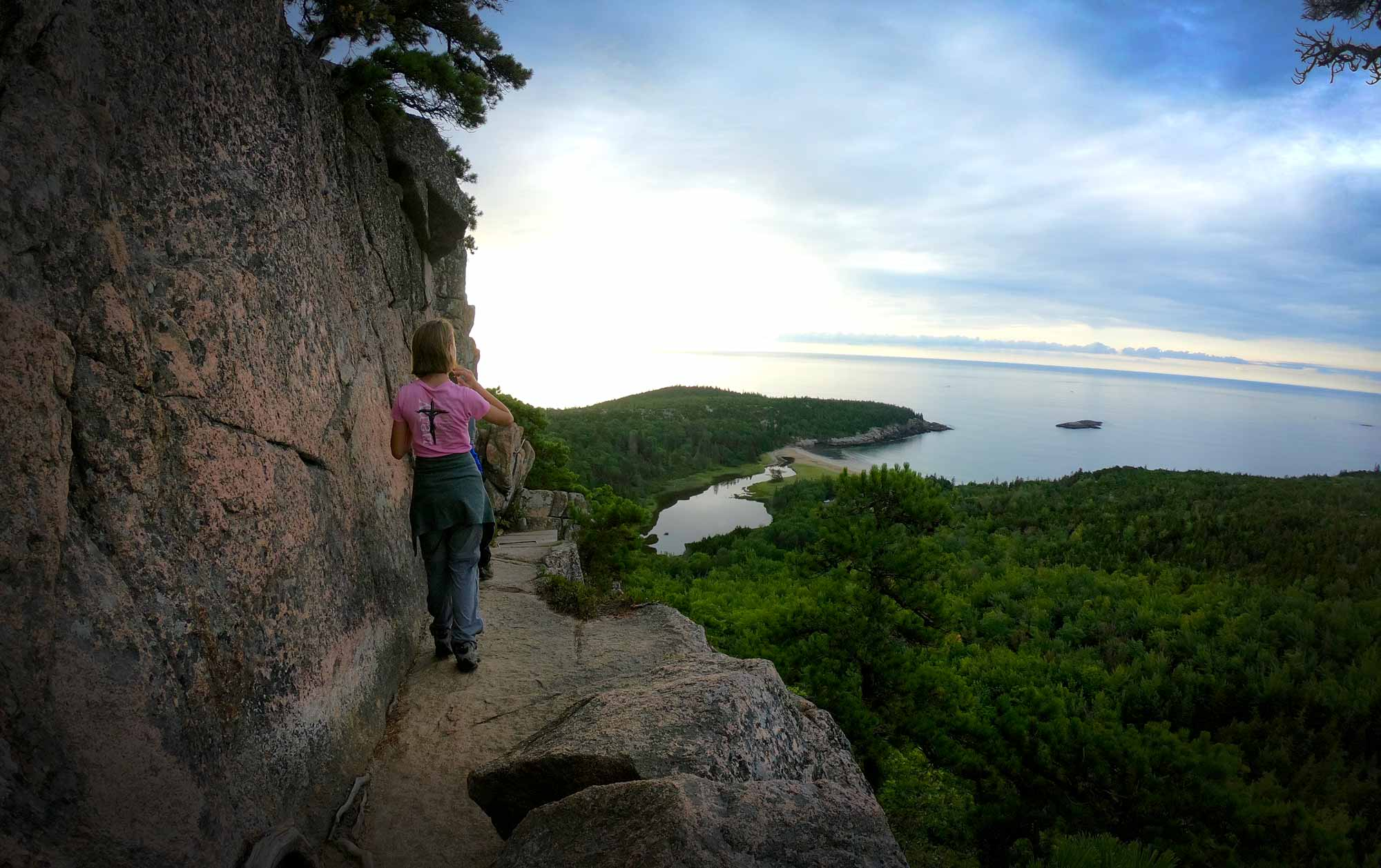 Teen walking at cliff's edge on Beehive Trail, Acadia National Park, Maine