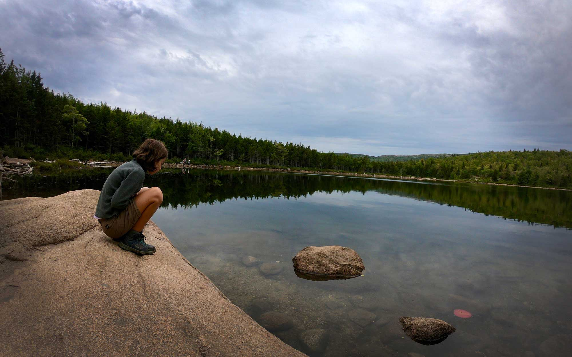 Teen looking into the clear lake water after hiking the Beehive Trail, Acadia National Park, Maine