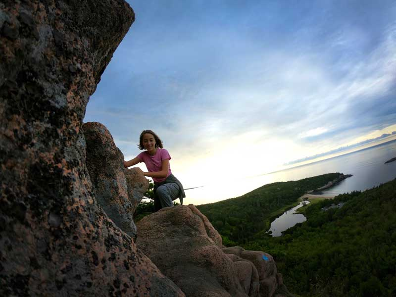 Hiker with sunrise behind her on the Beehive Trail, Acadia National Park, Maine