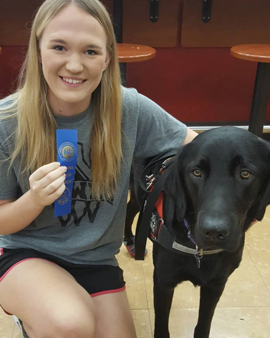 Girl with service dog presenting a ribbon for the dog.