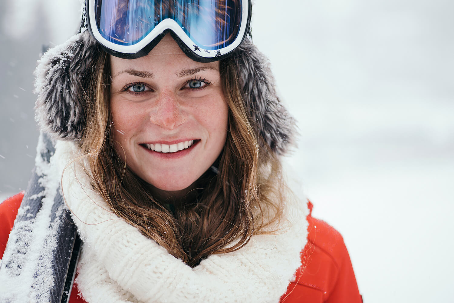 Portrait of a smiling woman in ski outfit and ski goggles