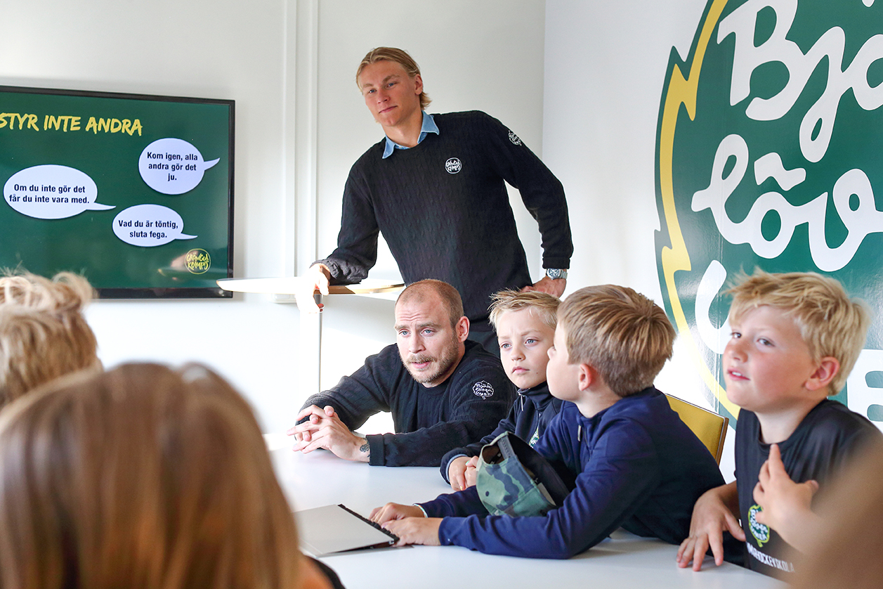 Two persons from Björklöven, a hockey team in Umeå, talking to a group of children