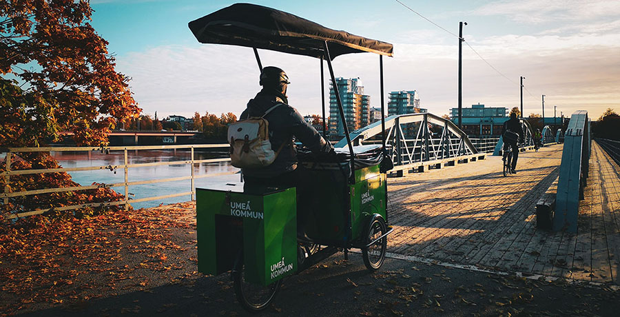 A person riding a green cargo bike and traveling over a bridge in Umeå
