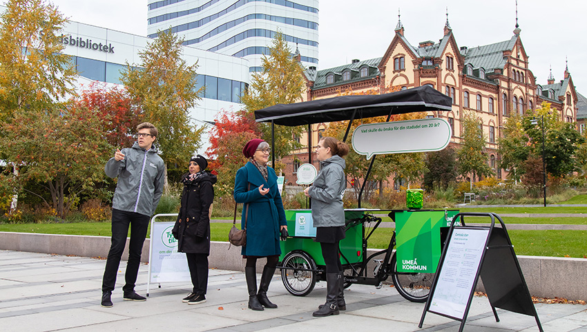 Four persons talking beside a green cargo bike in a park in Umeå city