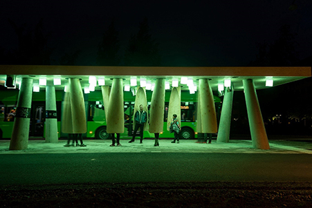 Seven people standing in the bus stop A Station of Being at night