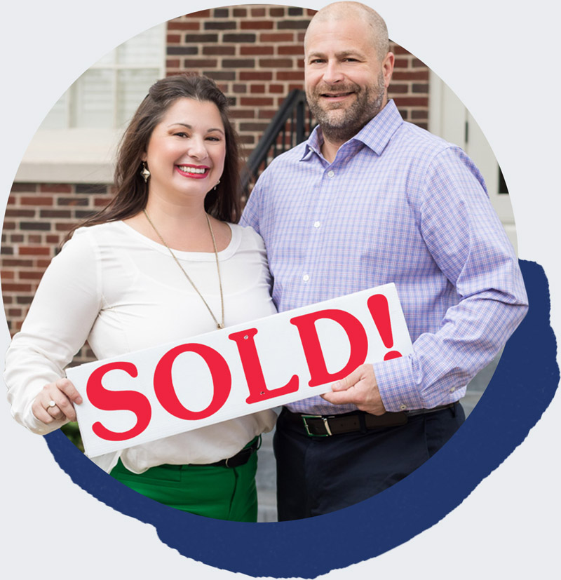 Tiffani and Brett hold a sold sign for a home
