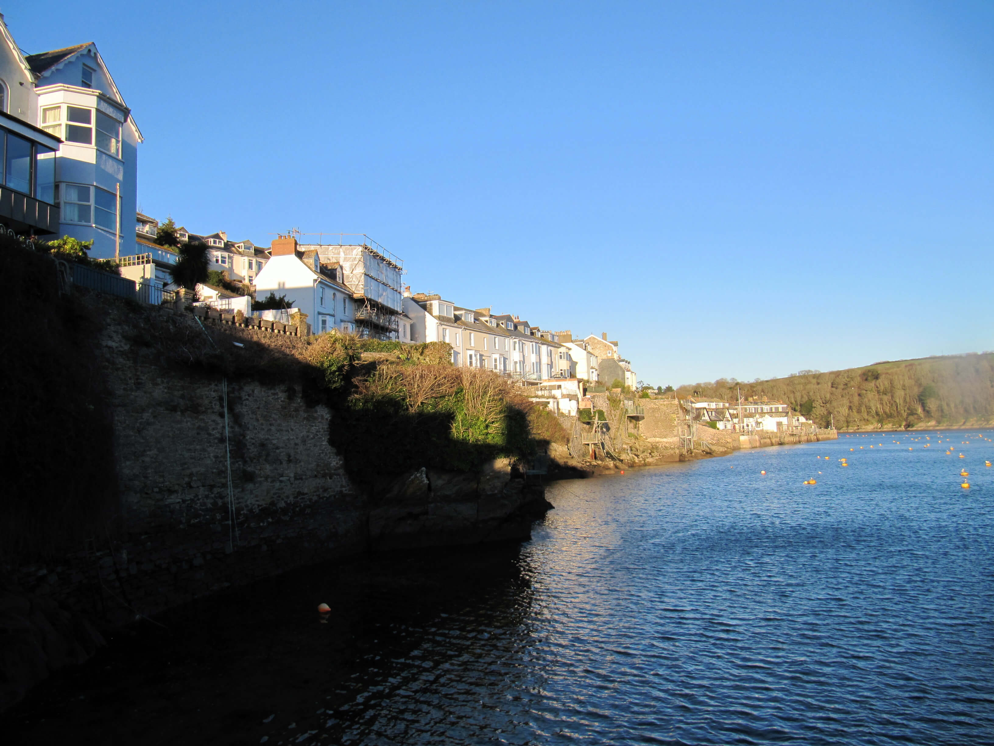 a group of homes towering above a bank by the bay on the Cornish Riviera