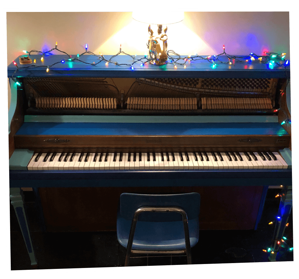 A blue Baldwin upright piano decorated with Christmas lights and a golden unicorn lamp.