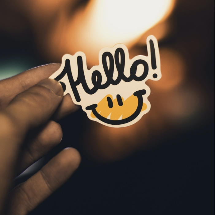 Person holding sticker that says Hello