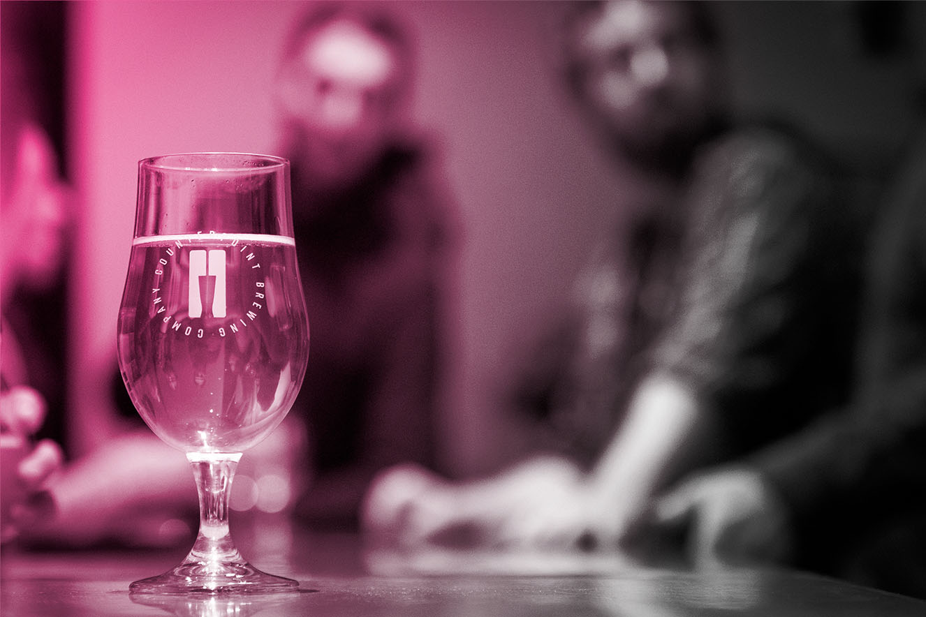 Image of a glass of beer with founders in the background, blurred
