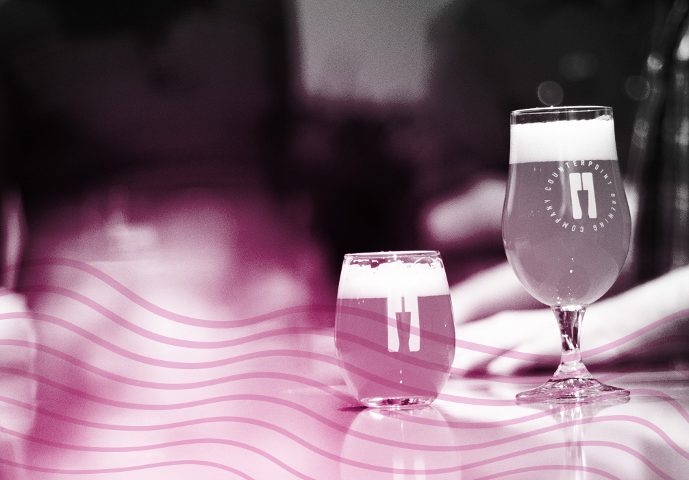 Image of two differently-shaped beer glasses on Counterpoint's bar counter.