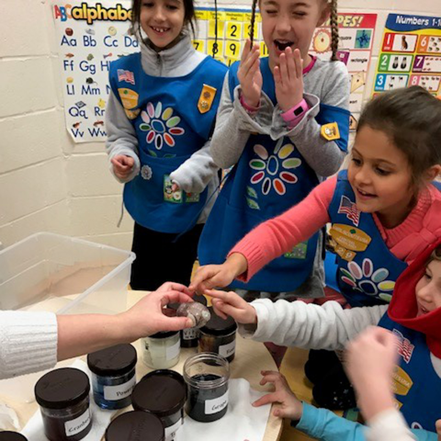 Girl Scouts touch an egg that is oozing from its membrane after its shell was eaten away by soaking in soda.