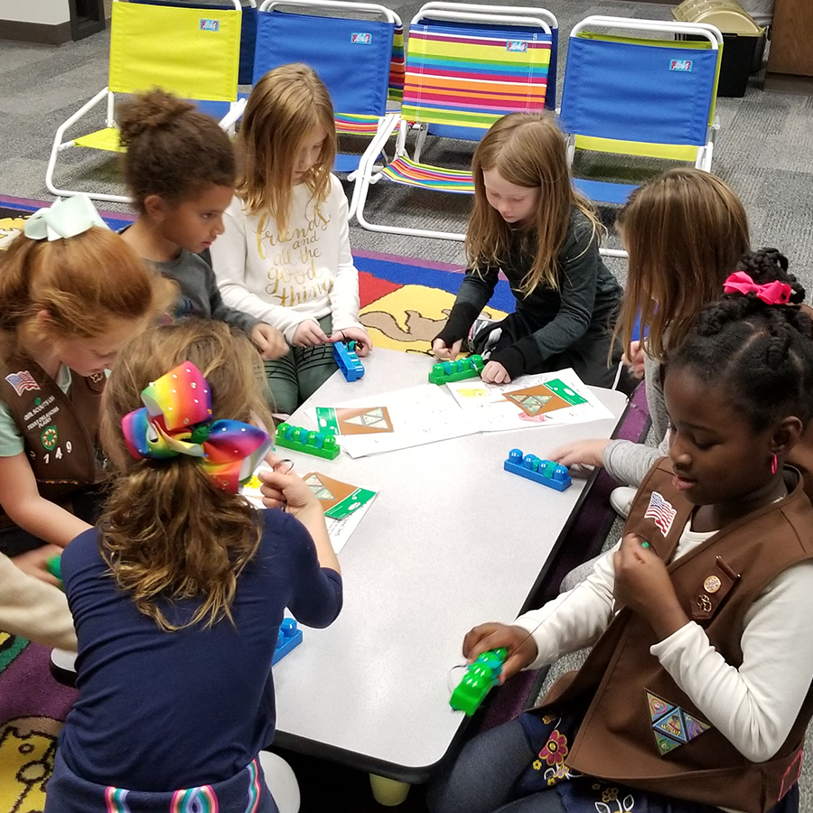 Girls use string to remove Play-Doh from between the bumps on Lego blocks to simulate flossing their teeth.