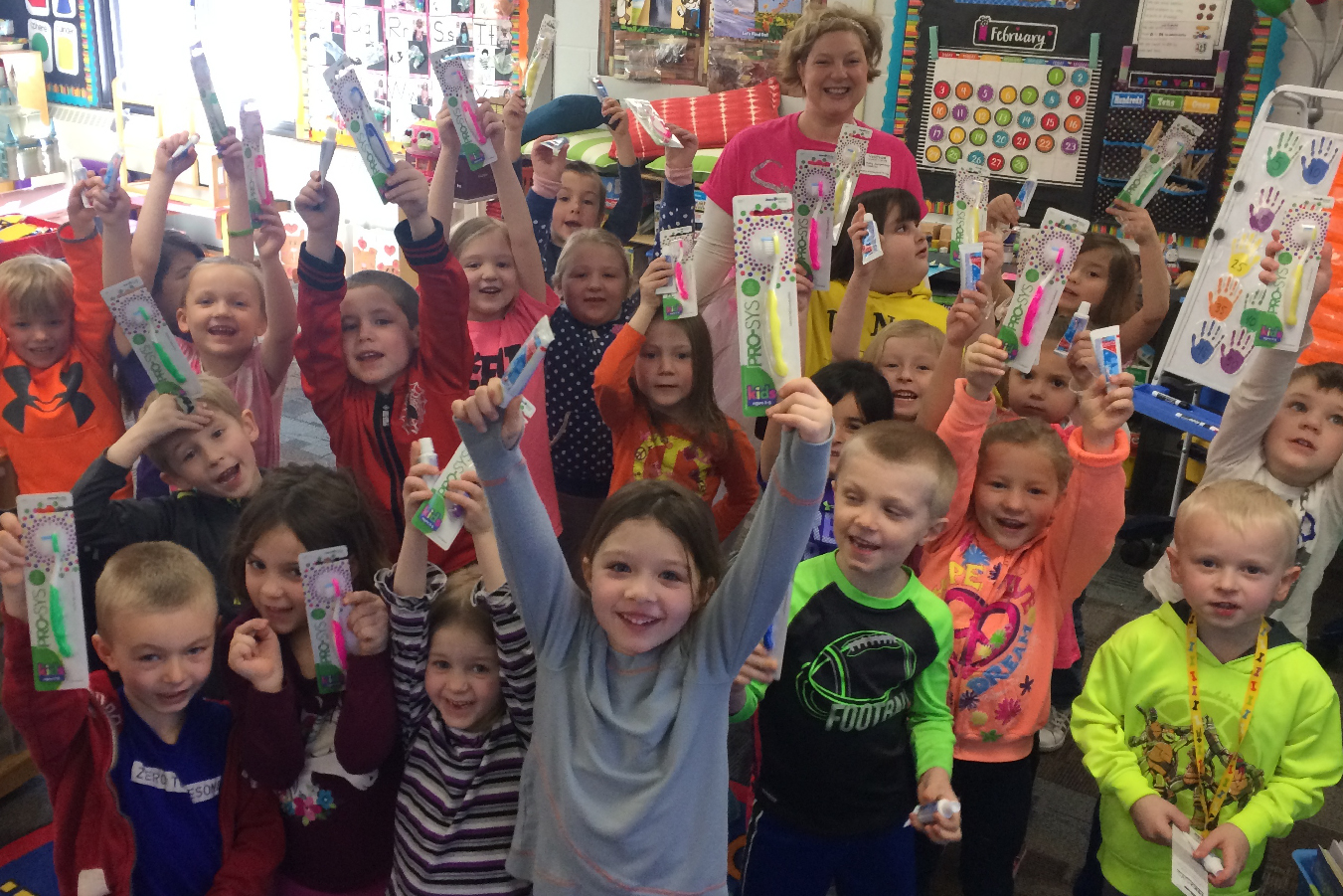 A group of children smile and show the toothbrushes and toothpaste they received from the Smile Fairy.