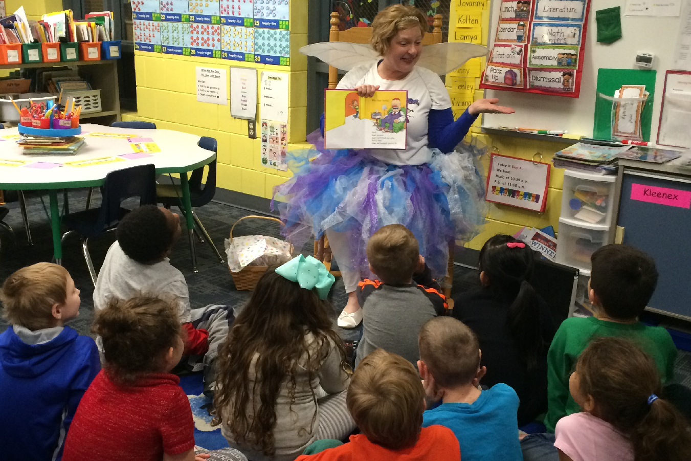 "The Smile Fairy displays the book ""The Tooth Book"" while reading it to students."