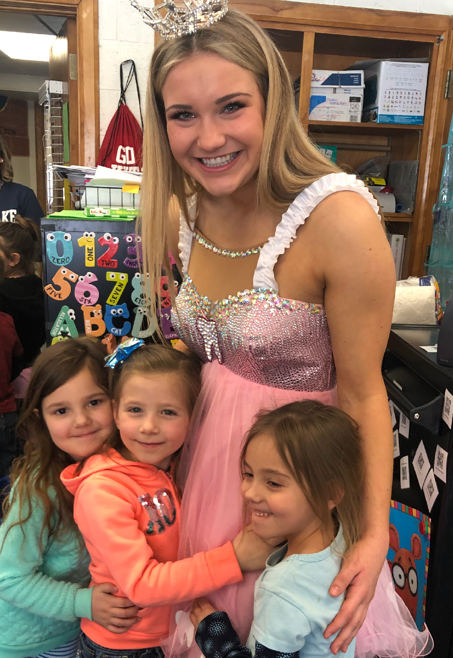 Three girls give Sophia Causie, dressed as the Tooth Fairy, a hug after her presentation.