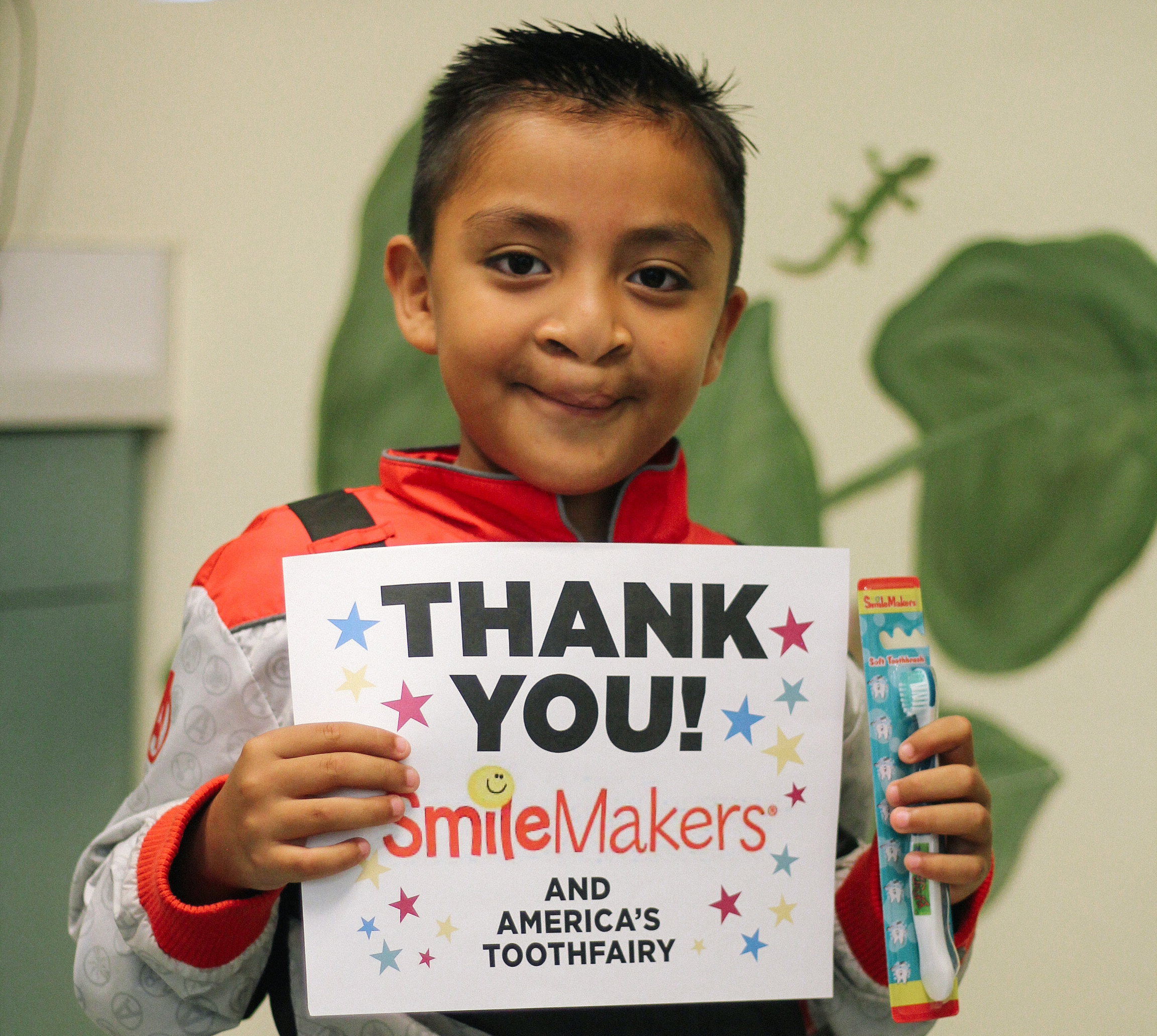 Boy with toothbrush holds up thank you sign for Smile Makers