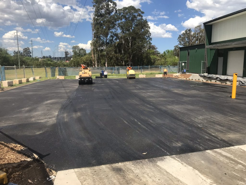 Three workers in the process of asphalting roads