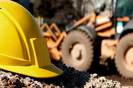 A yellow hard hat with a tractor in the background
