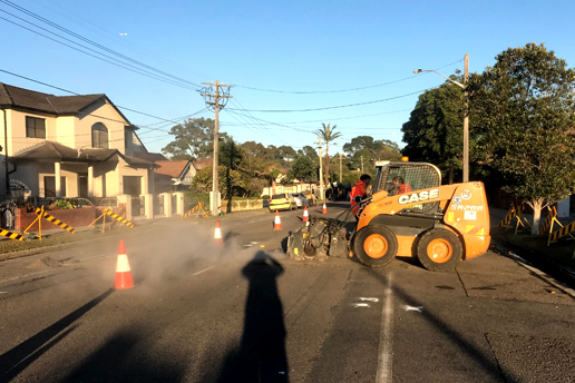 Two workers on a machine asphalting a road