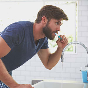 man brushing teeth to prevent toothaches