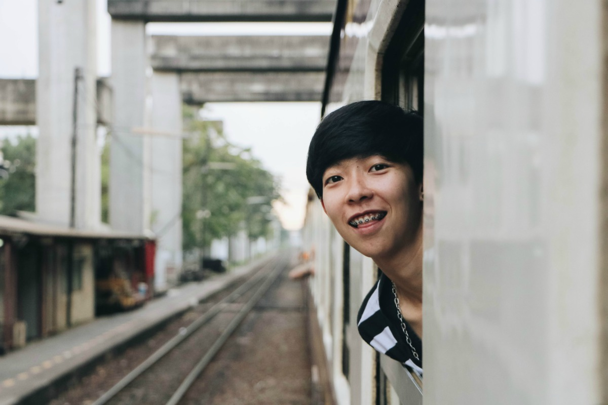 Boy with braces smiling out the window of a train