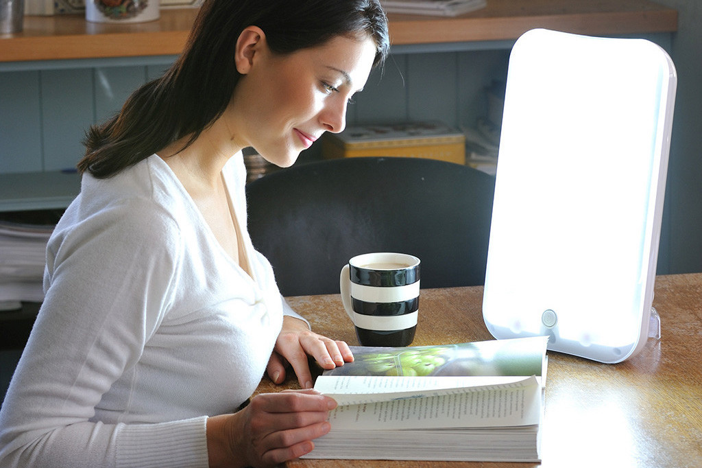 girl sitting in front on light therapy box in the morning