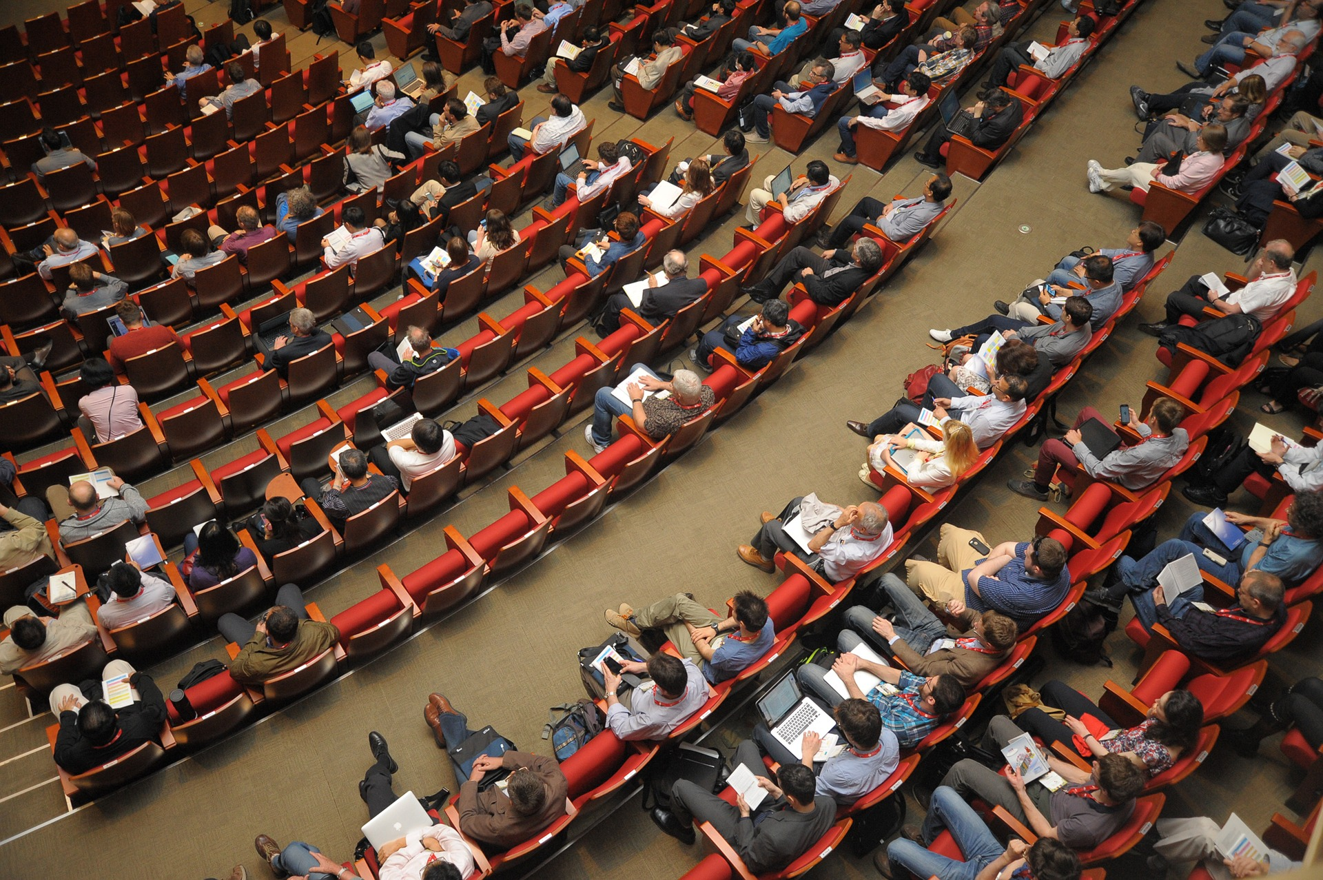 people taking notes in large lecture hall