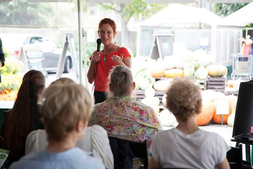a woman speaks about holistic mental health in front of a crowd