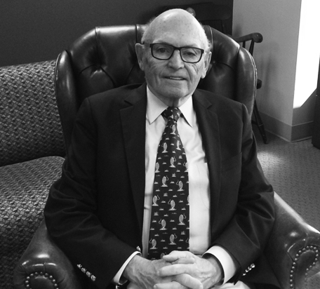 Dr Dunner, an older gentleman with glasses sitting in an armchair wearing a suit and tie, completed a review of TMS therapy as a depression treatment in his study for the university of washington.