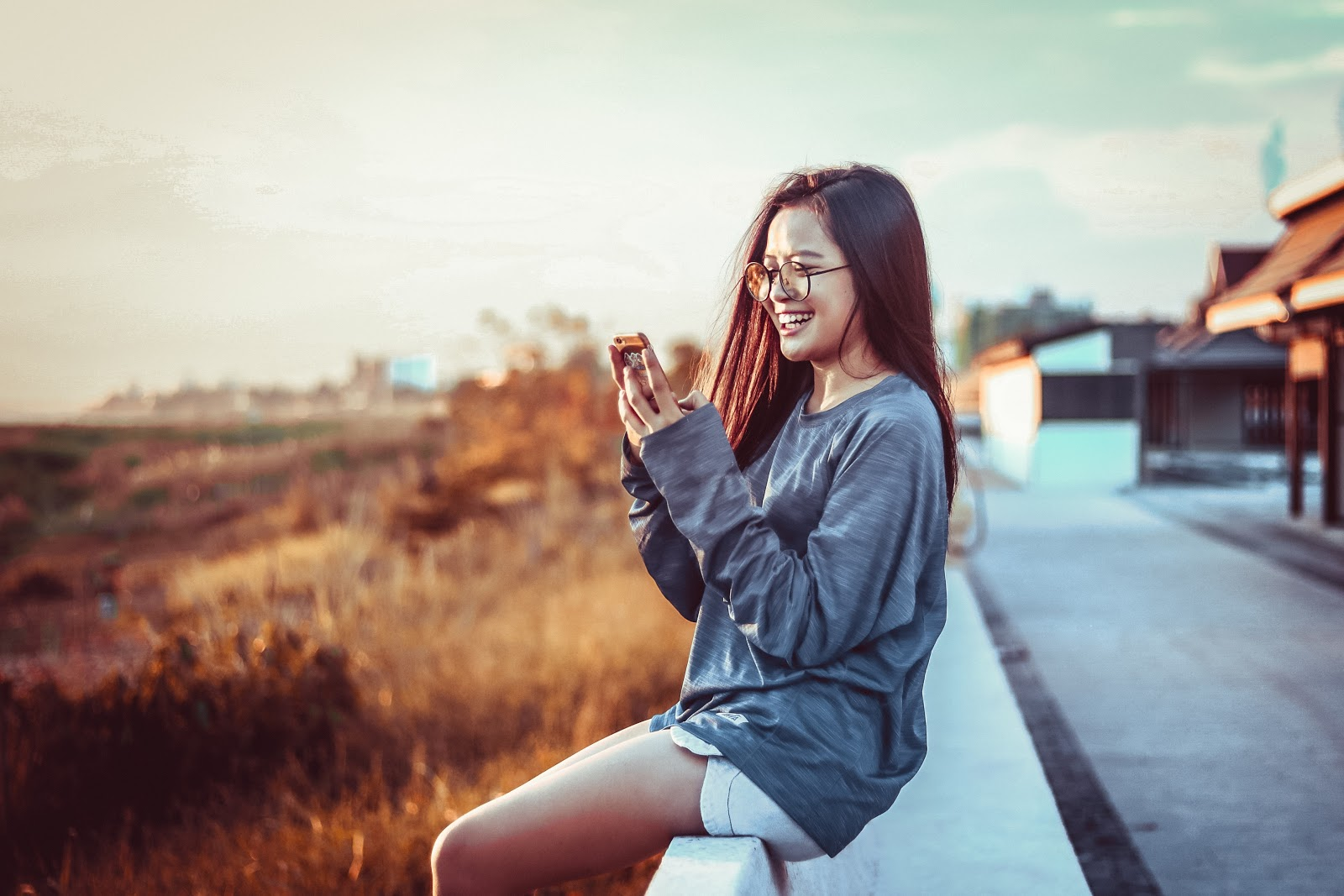 Woman sitting outside on her phone smiling